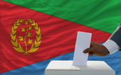 Man voting on elections in front of national flag of equatorial — Stockfoto