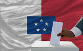 Man voting on elections in front of national flag of franceville — Stock Photo