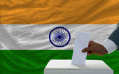 Man voting on elections in front of national flag of india — Photo