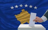 Man voting on elections in front of national flag of kosovo — Stock Photo