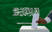 Man voting on elections in front of national flag of saudi arabi — Zdjęcie stockowe