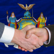 Stock Photo: In front of americstate flag of new york two businessmen hand