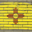 Grunge flag of US state of new mexico on brick wall painted with — Stock fotografie