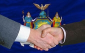 In front of american state flag of new york two businessmen hand — Stock Photo