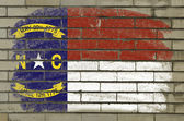 Grunge flag of US state of north carolina on brick wall painted — Stock Photo