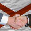 Stock Photo: In front of americstate flag of alabamtwo businessmen hands