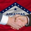 Stock Photo: In front of americstate flag of arkansas two businessmen hand