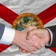 Stock Photo: In front of americstate flag of floridtwo businessmen hands