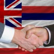 Stock Photo: In front of american state flag of hawaii two businessmen handsh
