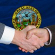 Stock Photo: In front of americstate flag of idaho two businessmen handsha
