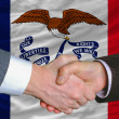 Stock Photo: In front of americstate flag of iowtwo businessmen handshak