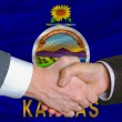 In front of american state flag of kansas two businessmen handsh — Stock Photo