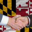 In front of american state flag of maryland two businessmen hand - Stock Photo