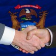 Stock Photo: In front of americstate flag of michigtwo businessmen hand