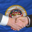 Stock Photo: In front of americstate flag of minnesottwo businessmen han
