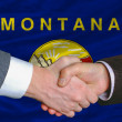 In front of american state flag of montana two businessmen hands — Stock Photo
