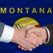In front of american state flag of montana two businessmen hands - Stock Photo