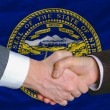 In front of american state flag of nebraska two businessmen hand — Stock Photo
