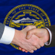 Stock Photo: In front of americstate flag of nebrasktwo businessmen hand