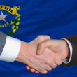 In front of american state flag of nevada two businessmen handsh — Stock Photo