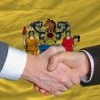 Stock Photo: In front of americstate flag of new jersey two businessmen ha