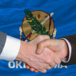In front of american state flag of oklahoma two businessmen hand - Foto Stock
