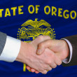 In front of american state flag of oregon two businessmen handsh - Foto Stock