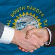 Stock Photo: In front of american state flag of south dakota two businessmen