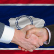Stock Photo: In front of americstate flag of wyoming two businessmen hands
