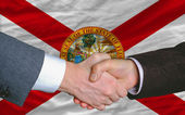 In front of american state flag of florida two businessmen hands — Stock Photo