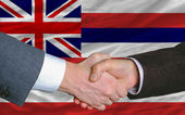 In front of american state flag of hawaii two businessmen handsh — Stock Photo