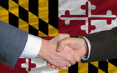 In front of american state flag of maryland two businessmen hand — Stock Photo