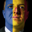 Face of serious businessman or politician painted in colors of a — Stock Photo #8800172