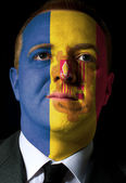 Face of serious businessman or politician painted in colors of a — Stock Photo