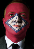 Us state of arkansas flag painted face of businessman or politic — Stock Photo