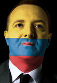 Face of serious businessman or politician painted in colors of c — Stock Photo