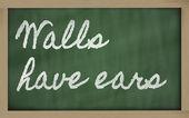 Expression - Walls have ears - written on a school blackboard w — Stock Photo