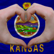 Stock Photo: Over americstate flag of kansas showed heart and love gesture