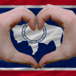 Stock Photo: Over americstate flag of wyoming showed heart and love gestur