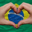 Royalty-Free Stock Photo: Over national flag of brazil showed heart and love gesture made