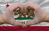Over american state flag of california showed heart and love ges — Stock Photo