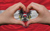 Over national flag of austria showed heart and love gesture made — Stock Photo