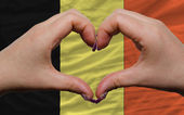 Over national flag of belgium showed heart and love gesture made — Stock Photo