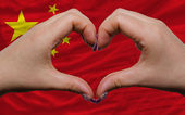 Over national flag of china showed heart and love gesture made b — Stock Photo