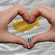 Stock Photo: Over national flag of cyprus showed heart and love gesture made