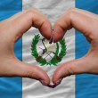 Stock Photo: Over national flag of guatemalshowed heart and love gesture ma