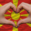 Stock Photo: Over national flag of macedonishowed heart and love gesture ma
