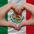 Stock Photo: Over national flag of mexico showed heart and love gesture made