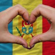 Stock Photo: Over national flag of moldovshowed heart and love gesture made