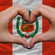 Over national flag of peru showed heart and love gesture made by - Zdjęcie stockowe